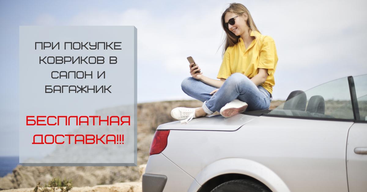 На фото довольная девушка-покупатель автоковриков сидит на багажнике автомобиля и читает сообщение с мобильного телефона