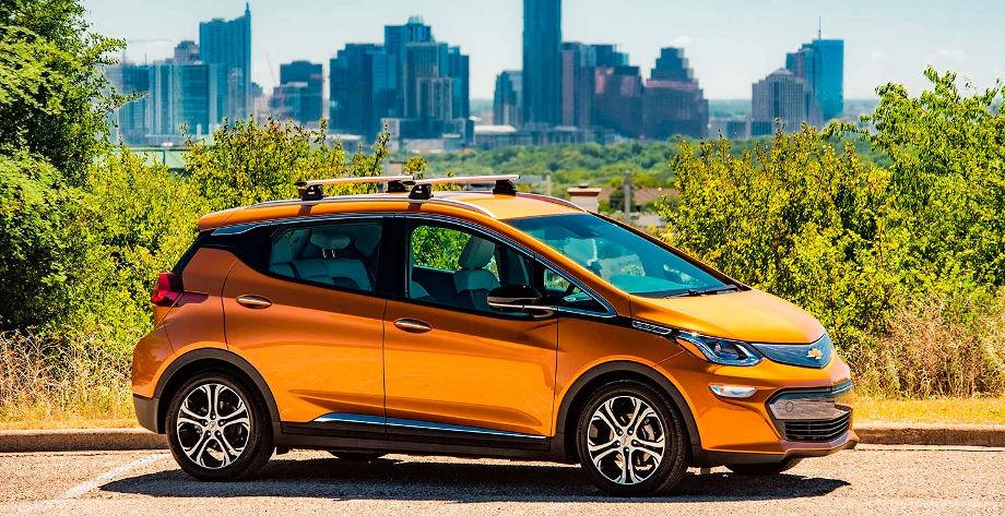 на фотографии электромобиль Chevrolet Bolt оранжевого цвета, за ним вдалеке многоэтажки