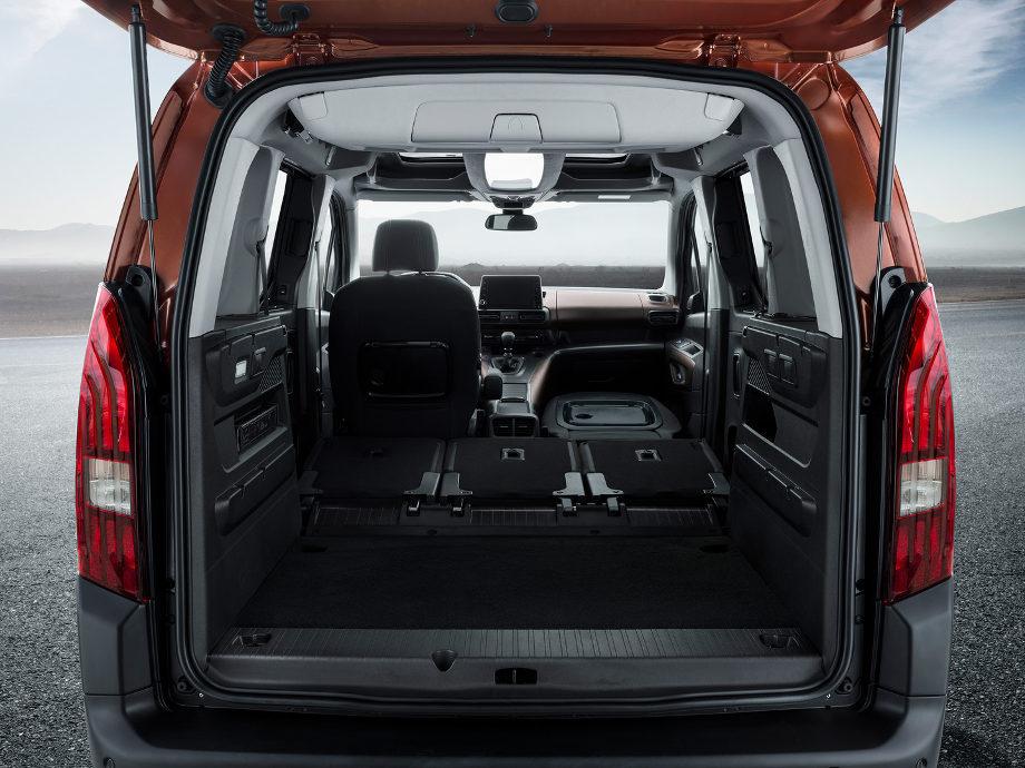 На фото через открытый багажник автомобиля Peugeot Rifter 2018 виден салон со сложенными сидениями