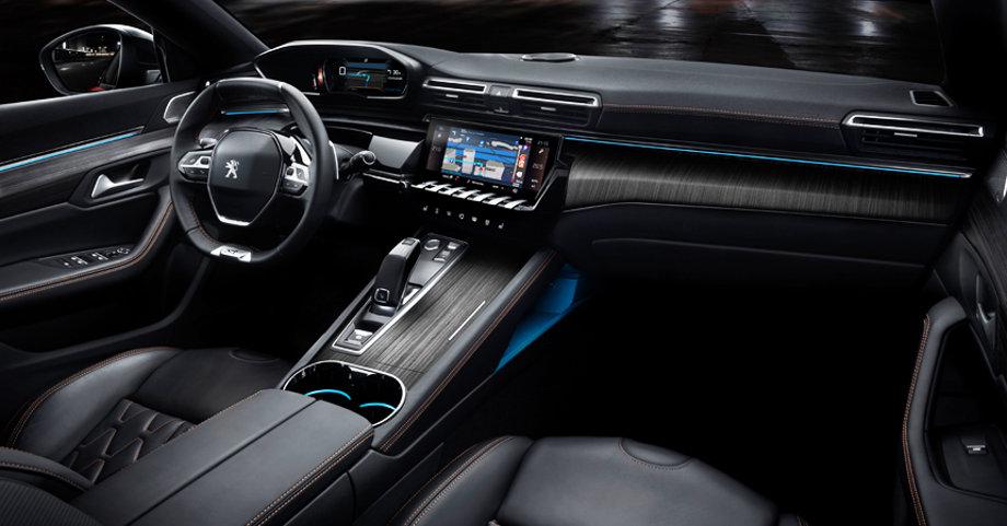 На фотографии часть чистого салона автомобиля Peugeot 508 с 2018 года, видна передняя панель, водительское и пассажирское сидение, руль, коробка передач. Чтобы салон выглядел ухоженым, необходимо купить резиновый коврик в машину