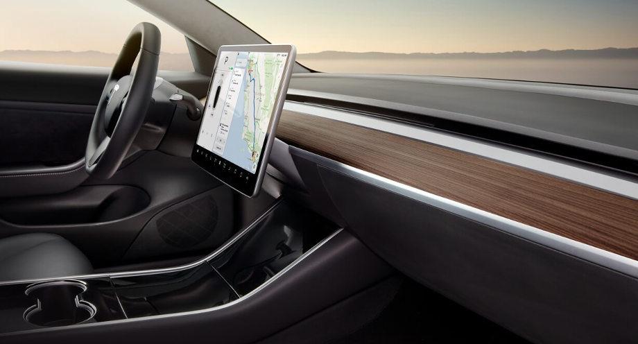 На фото вид справа на торпеду с дисплеем в салоне серого цвета автомобиля Тесла Модель 3