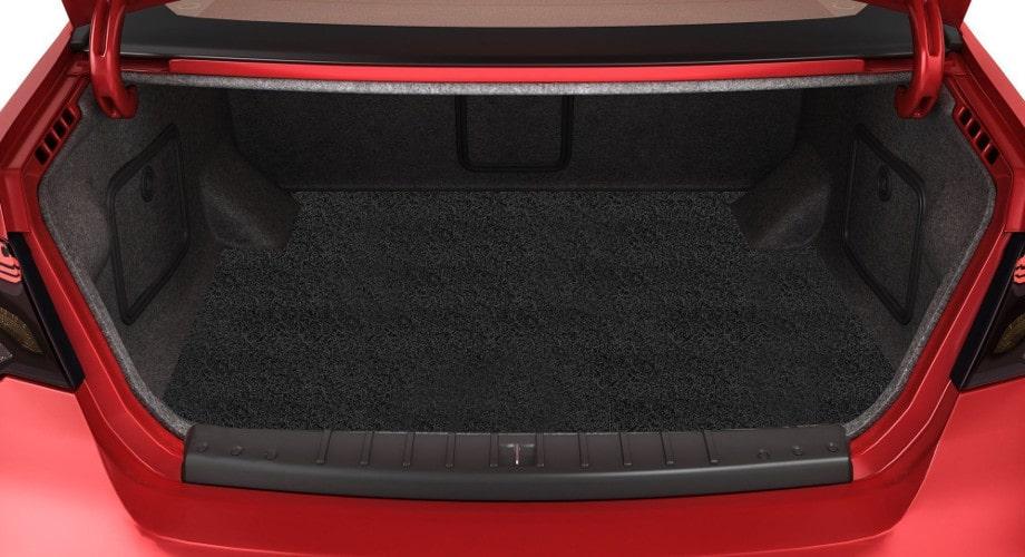 Купить коврик в багажник. На фото черный ворсовый коарик в багажнике автомобиля красного цвета
