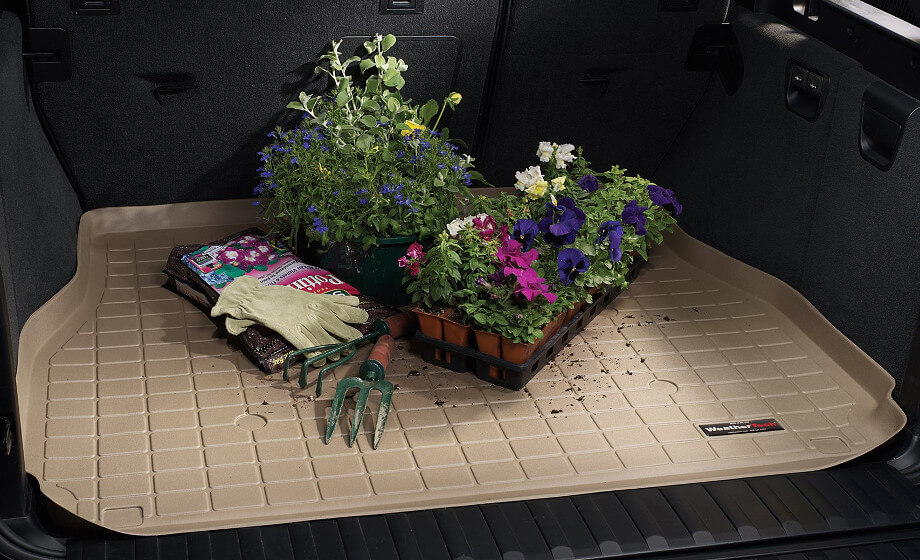 на фотографии коврик в багажник автомобиля, на нем стоят вазоны с цветами, рассыпана земля, коврик в багажник защищает от царапин и грязи