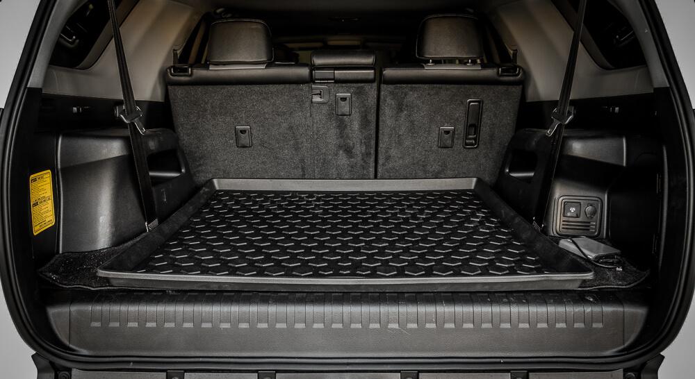 На фотографии пластиковый коврик в багажник автомобиля, коврик расположен в отсеке багажника. Коврик черного цвета, с бортиком около четырех сантиметров.