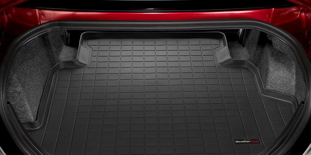 На фотографии полиуретановый коврик в багажник автомобиля, коврик расположен в отсеке багажника. Коврик черного цвета, с бортиком около трех сантиметров