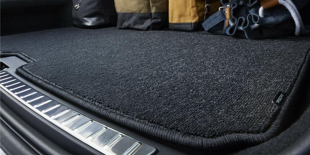 На фото ворсовый коврик в багажник автомобиля, коврик расположен в отсеке багажника. На нем расположены рюкзак и сумки, песочного цвета. Сам коврик темно-серого цвета и отлично ложится на дно багажника