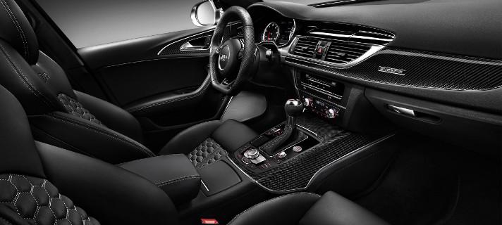 На фотографии ухоженный салон автомобиля KIA Rio черного цвета. Он чистый благодаря автомобильным резиновым коврикам