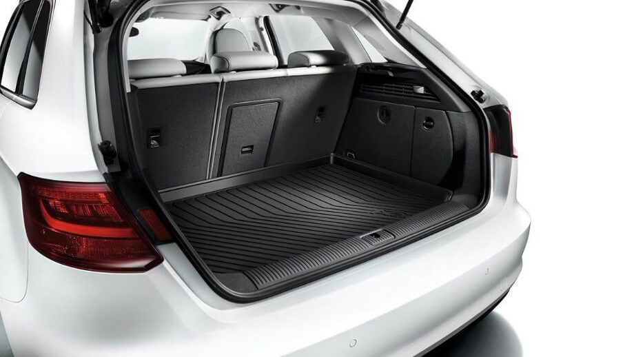 На фото автомобиль Ауди А3, белого цвета, вид сзади. Багажник в открытом положении, прямо перед глазами коврик Ауди