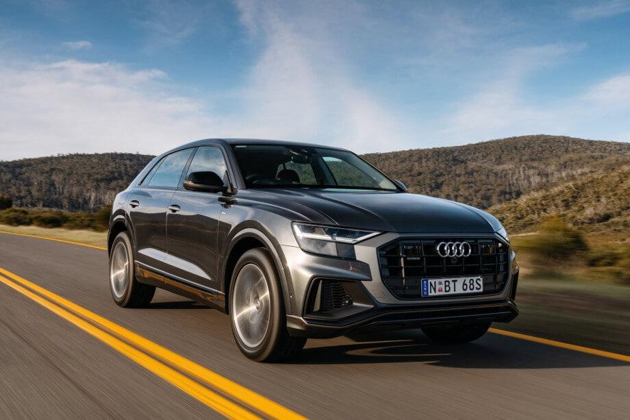 На фото автомобиль Ауди Q8, темно-серого цвета. Audi мчится по шоссе, на заднем плане голубое небо и красивые холмы