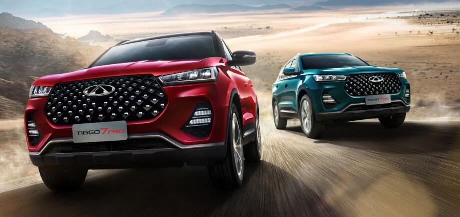 На фото два автомобиля Chery Tiggo 7. Они мчатся по сельской местности, обгоняя друг друга.