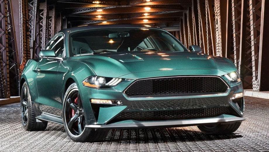 На фото автомобиль Форд Мустанг, зеленого цвета. Это мощное спортивное авто расположено на металлическом мосту.