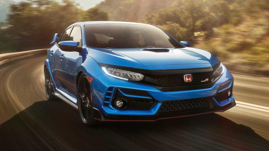 На фото Хонда Цивик синего цвета. Она на огромной скорости выезжает из поворота