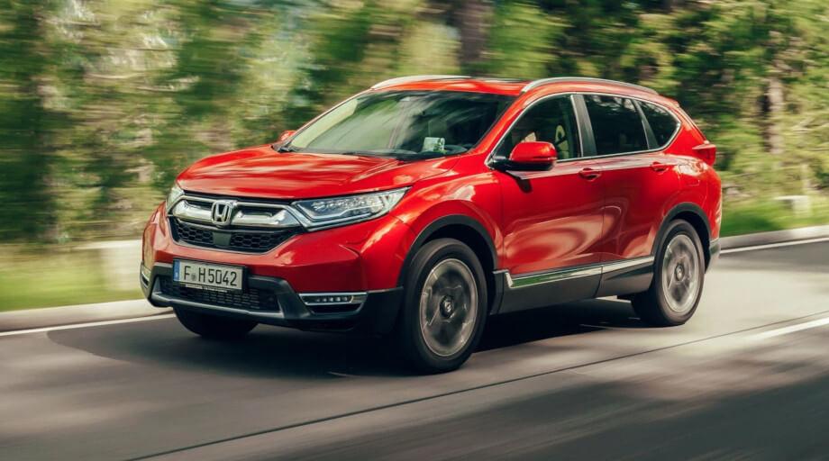 На фото Хонда CR-V красного цвета. Автомобиль проезжает участок дороги расположенный в лесу