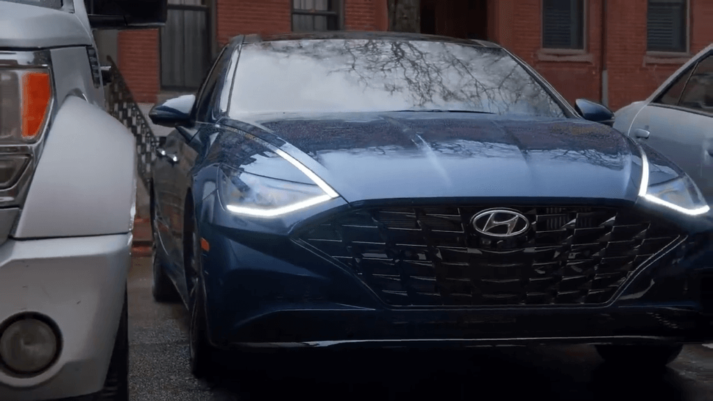 На фото автомобиль Хендай Соната 2020 года, синего цвета. Он паркуется благодаря умной системе парковки без водителя