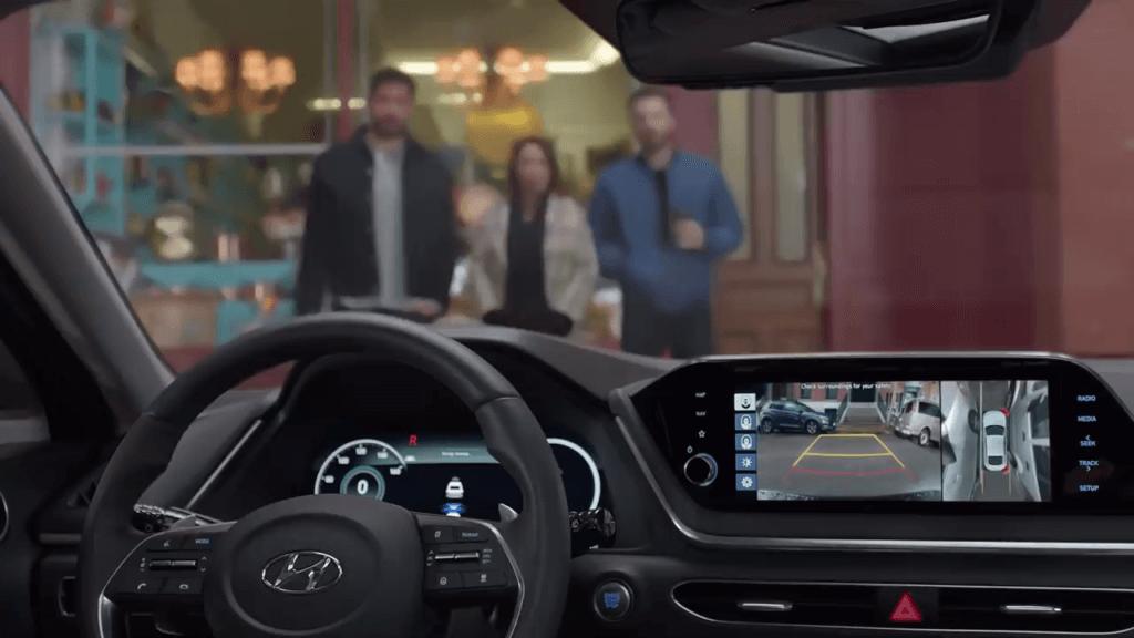На фото приборная панель автомобиля Хендай Соната 2020 года. Он паркуется благодаря умной системе парковки без водителя. Впереди стоит владелец авто и случайные пешеходы.