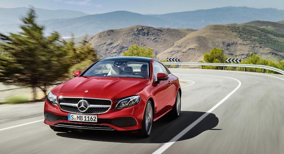 На фото автомобиль Mercedes-Benz coupe. Машина красного цвета в движении, за рулем женщина. Вокруг дороги живописная местность, горы и извилистая трасса