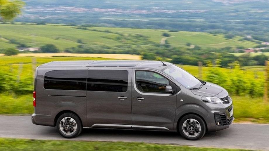 На фото микроавтобус Опель серого цвета в движении на загородной дороге