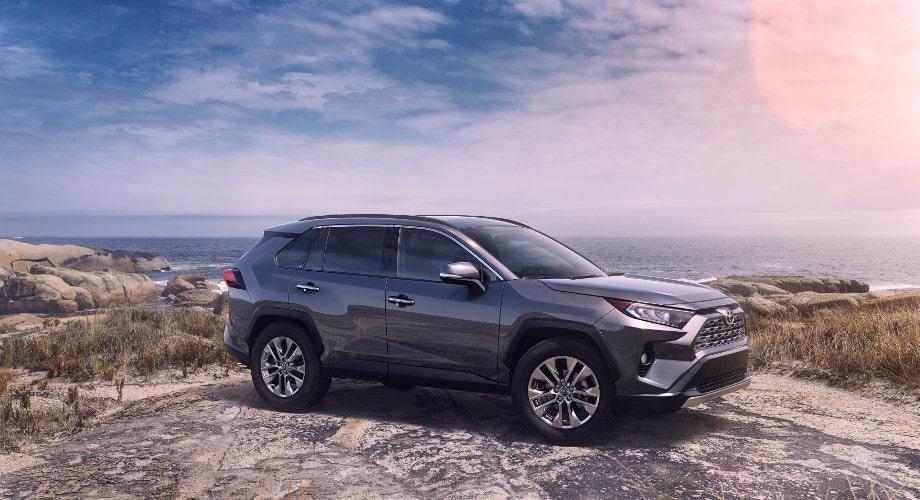 Автомобильные коврики Тойота. На фото внедорожник Тойота Рав 4. Он стоит на фоне моря и гор. Сзади голубое небо с облаками