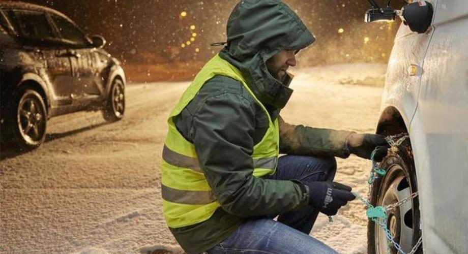 На фото водитель в сигнальном жилете зимним вечером устанавливает цепи противоскольжения на переднее колесо автомобиля