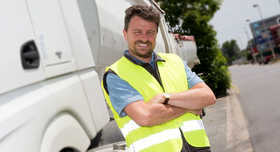 На фото водитель в светоотражающем жилете безопасности стоит на обочине возле кабины грузового автомобиля белого цвета