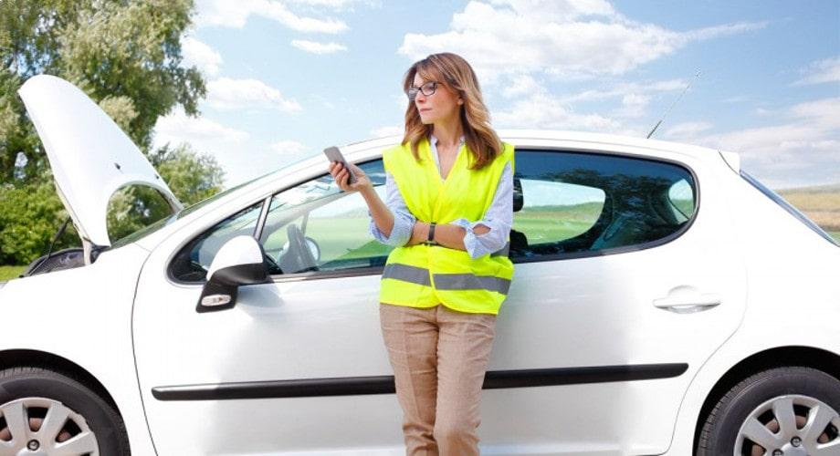 На фото женщина в люминисцентном жилете безопасности стоит на обочине возле поломанной белой машины, набирает номер на телефоне