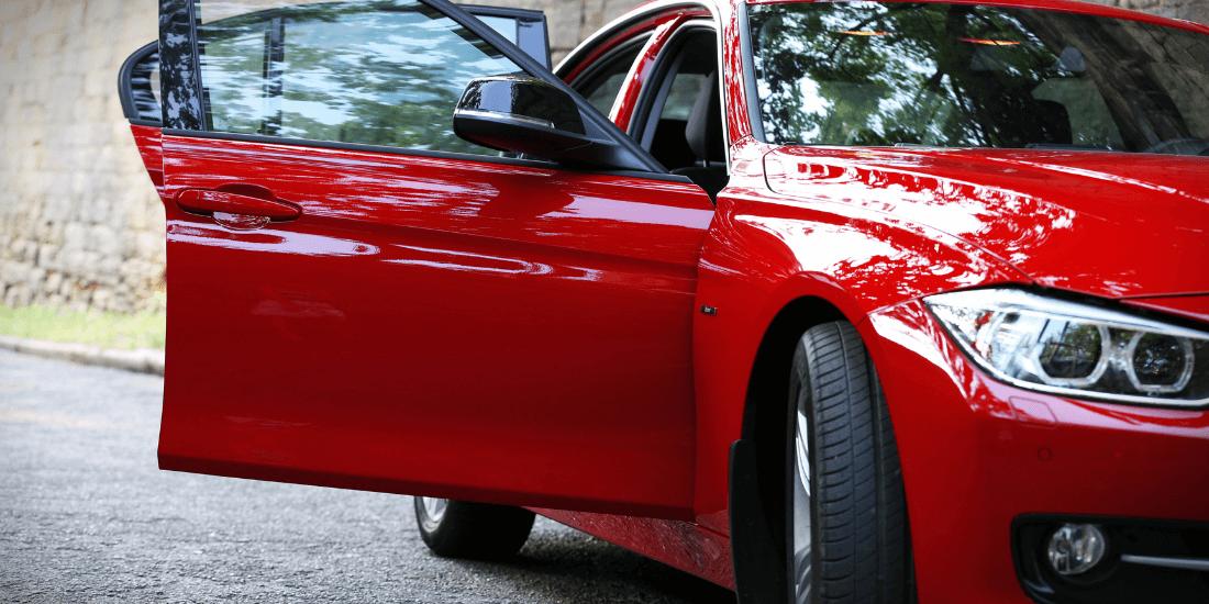 На фото авто красного цвета с открытыми дверьми, машина проветривается перед включением кондиционера