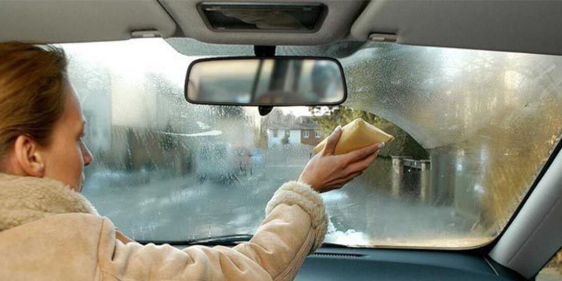 На фото женщина-водитель протирает губкой лобовое стекло изнутри автомобиля, чтобы потом нанести средство против конденсата