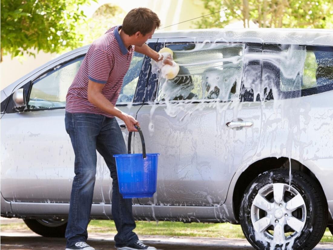 На фото мужчина автомобилист моет машину в домашних условиях. Он выполняет губкой прямые движения.