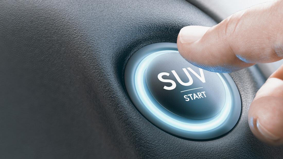На фото большой палец правой руки водителя нажимает на кнопку полного привода с надписью SUV