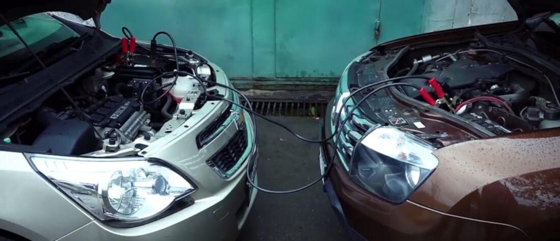 На фото два автомобиля во время прикуривания. Они находятся друг возле друга и соеденены высоковольтными проводами для прикуривания