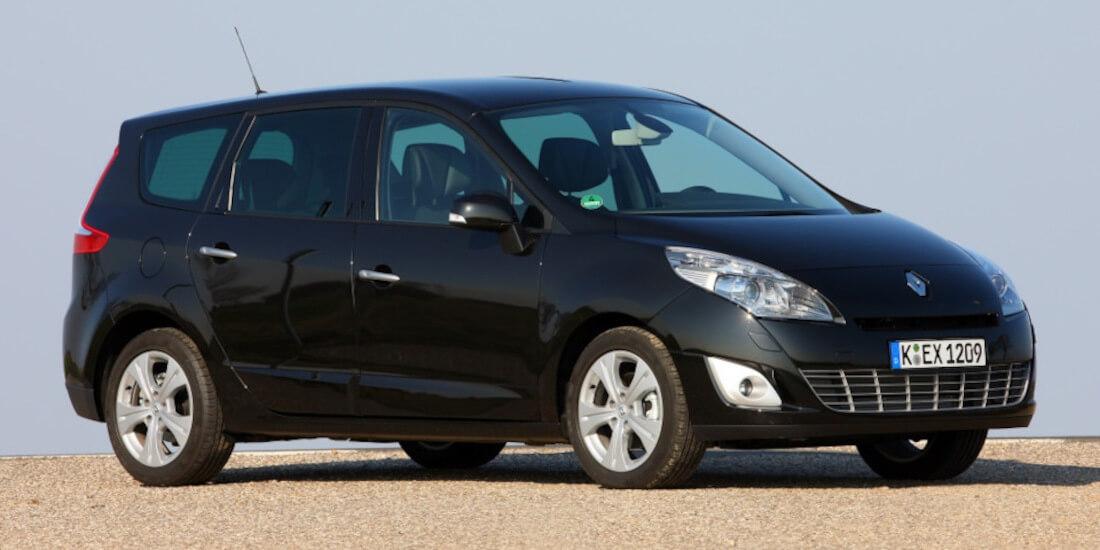 На фото семейный автомобиль Рено Сценик черного цвета, на однотонном фоне