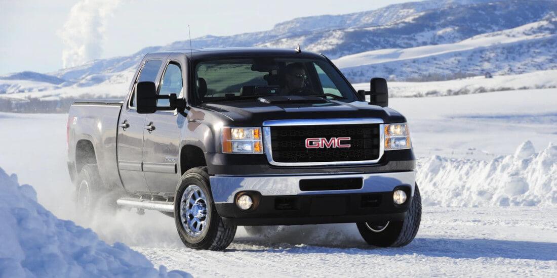 На фото зимнее вождение на автомобиле GMC. На фоне горного пейзажа