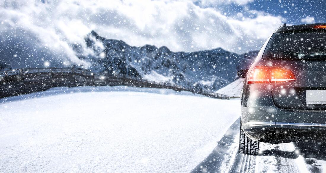 На фото зимнее вождение, идет снег. Автомобиль притормаживает