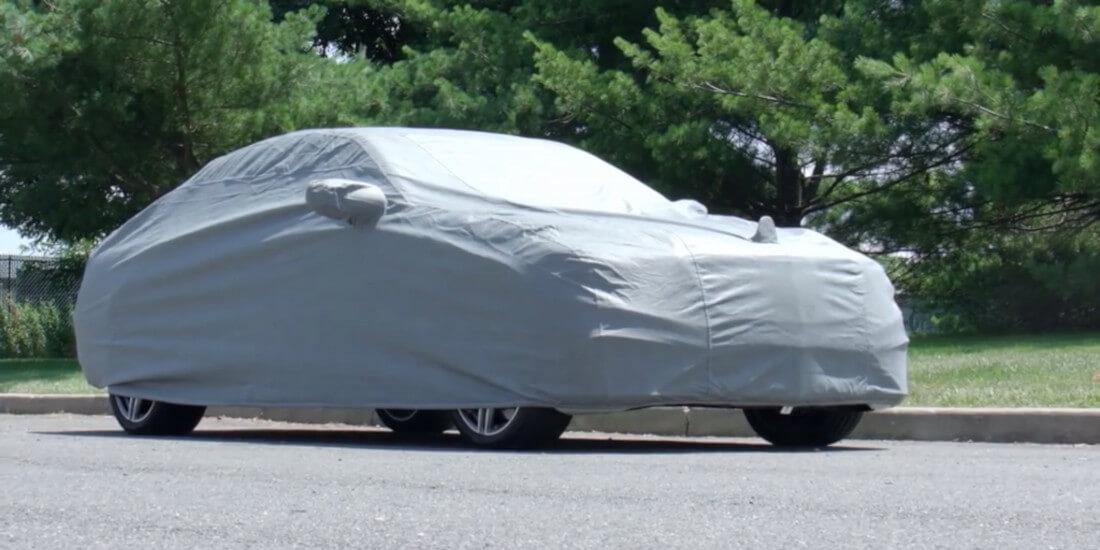 На фото автомобіль Мерседес під тентом світло-сірого кольору. Він захищає лако-фарбове покриття від ультрафіолету