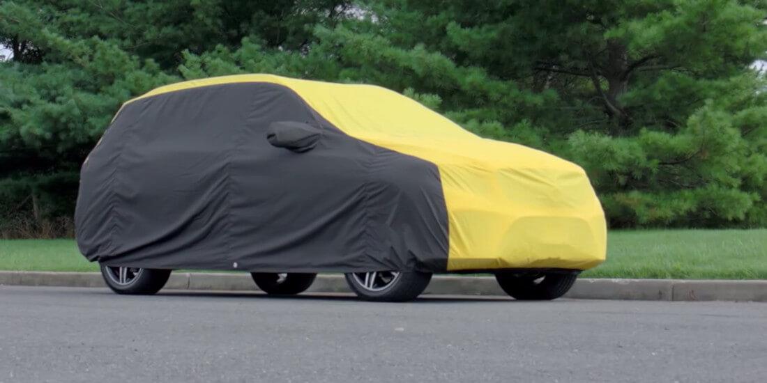 На фото автомобіль під тентом чорно-жовтого кольору. Чохол пошитий з урахуванням конструкції машини