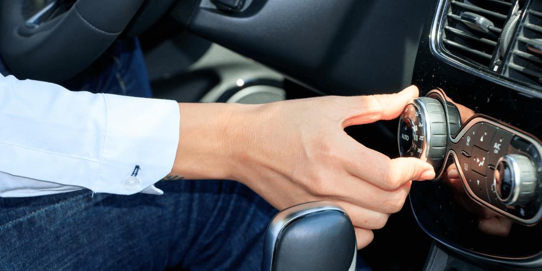На фото водитель ключает кондиционер. Он тянется рукой к регулятору
