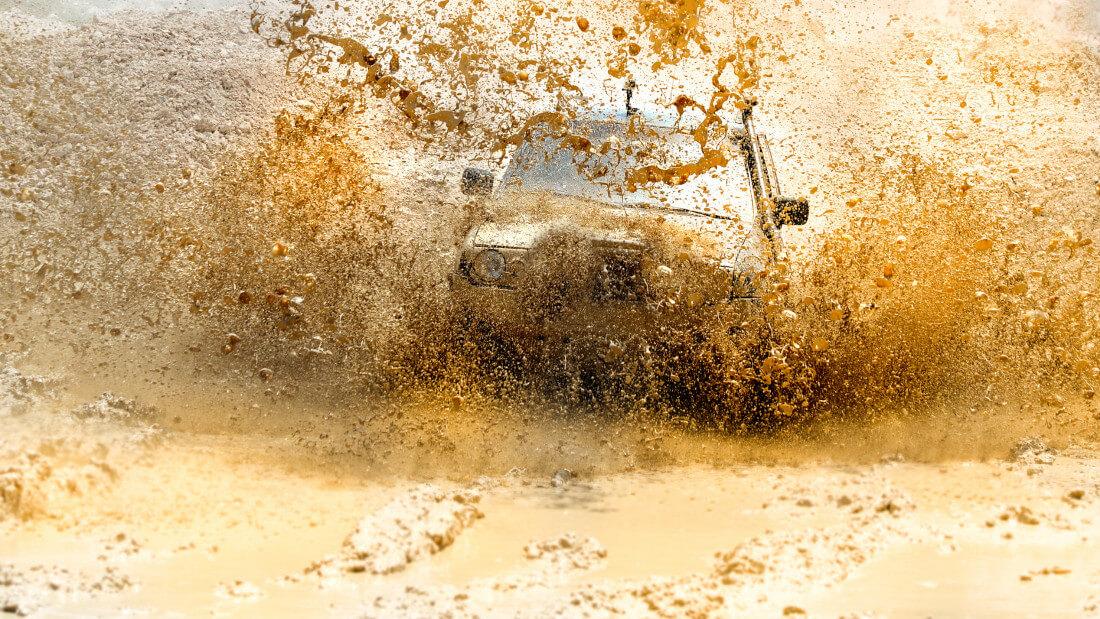 На фото внедорожник который едет через грязную лужу, брызги разлетаются в разные стороны