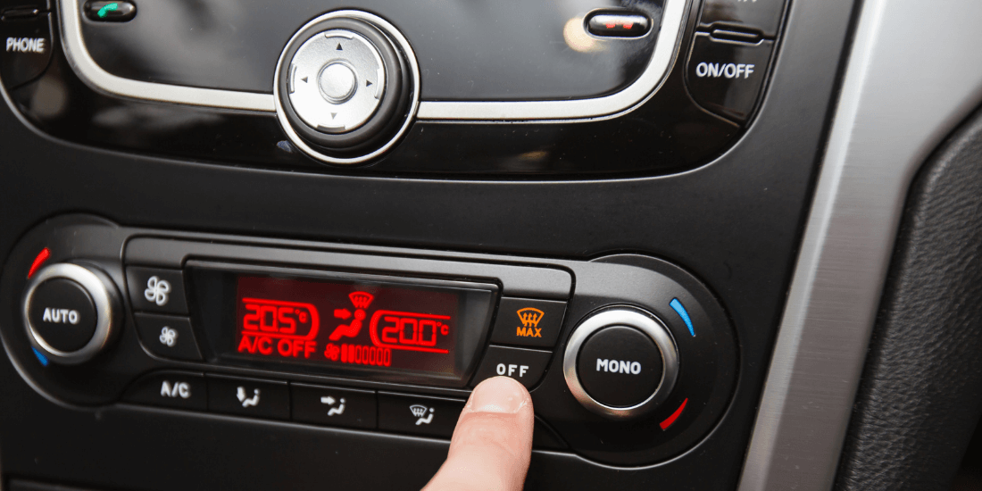 На фото водитель выключает автомобильный кондиционер. Он протягивает руку к цифровой панели и нажимает кнопку