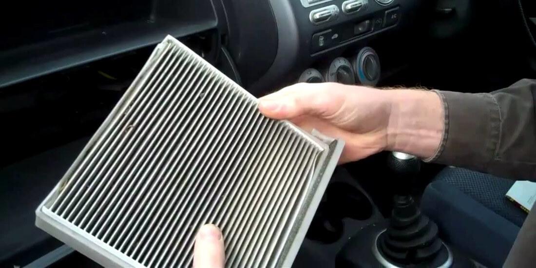 На фото водитель делает замену в автомобиле салонного фильтра, который уже загрязнился