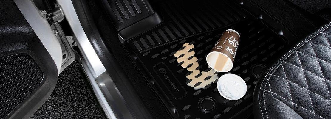 на фото бумажный стакан, из которого разливается кофе на полимерный коврик, возле сиденья водителя