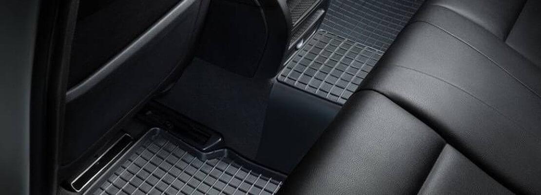 на фото автомобильный коврик заднего сиденья с перемычкой, они черного цвета и имеют ячеистую структуру