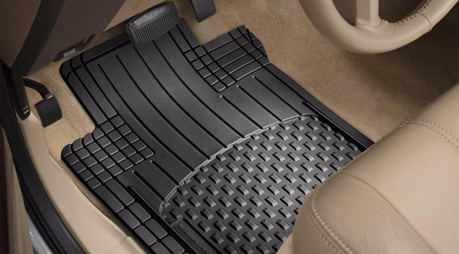 На фотографии часть чистого салона автомобиля, виден резиновый коврик черного цвета, руль, также педали газа и тормоза. Чтобы салон выглядел ухоженым, необходимо купить резиновый коврик в машину