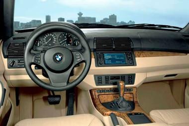 На фото салон автомобиля БМВ Х5 Е53 светлого цвета с новыми резиновыми ковриками