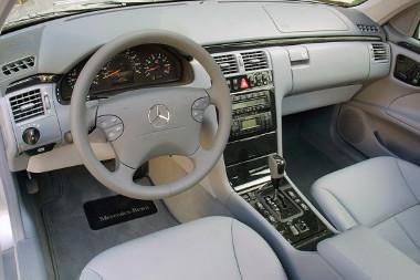 На фотографии салон автомобиля Мерседес Е-класса W210 бежевого цвета с ворсовыми ковриками