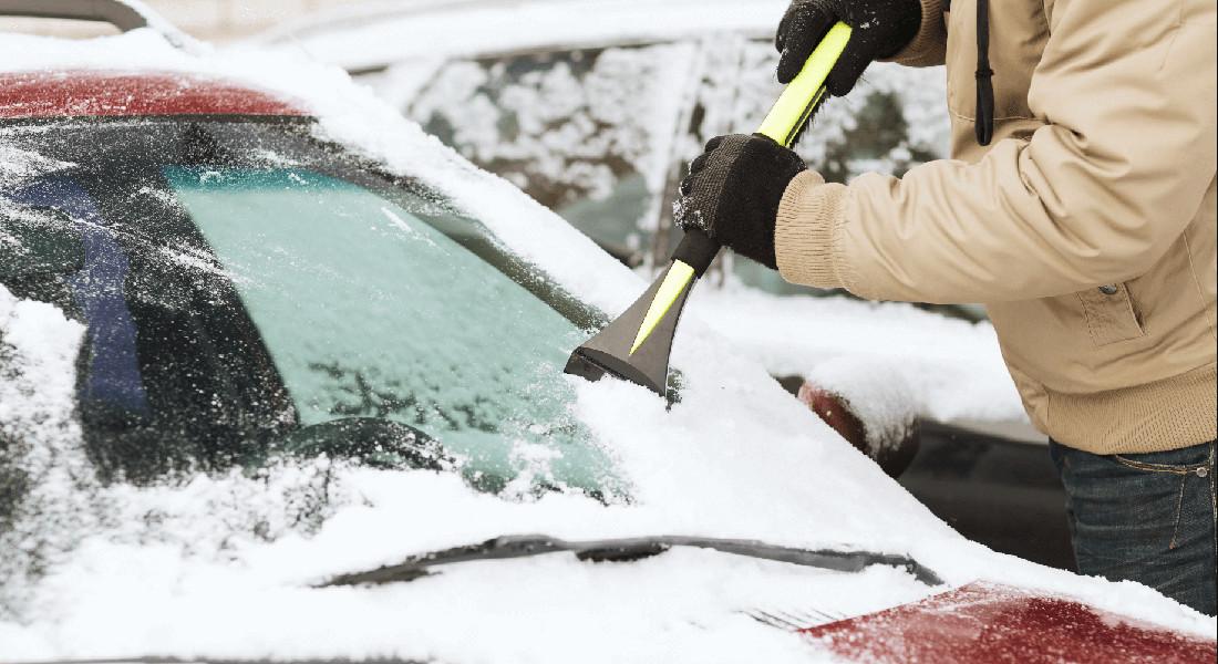На фото машина присыпана снегом, автомобилист при помощи щетки и скребка очищает лобовое стекло автомобиля от льда