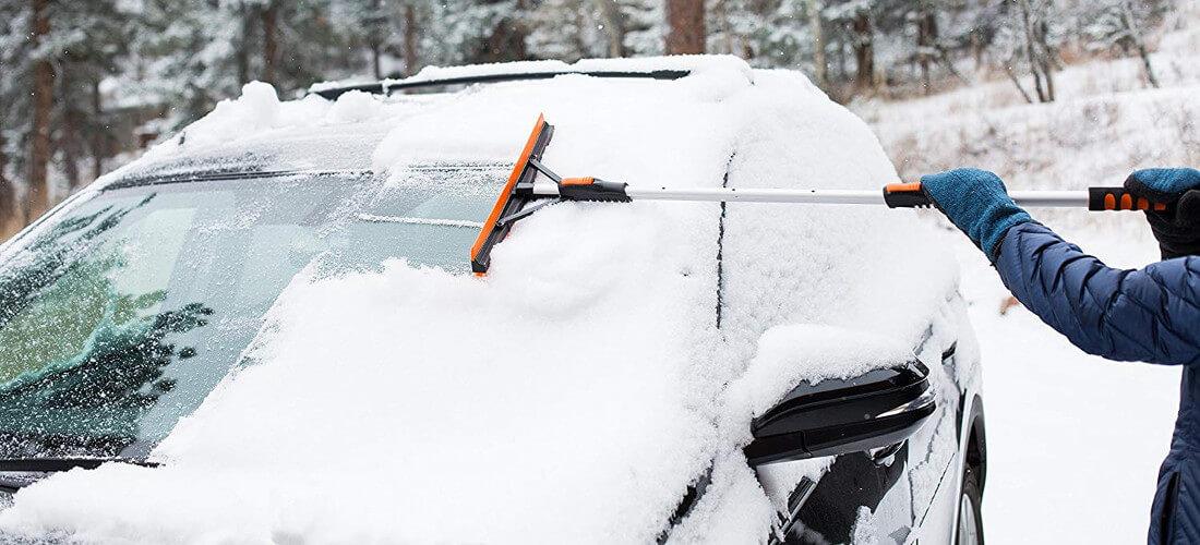 На фото машина присыпана снегом, автомобилист при помощи щетки и скребка очищает лобовое стекло автомобиля от снега