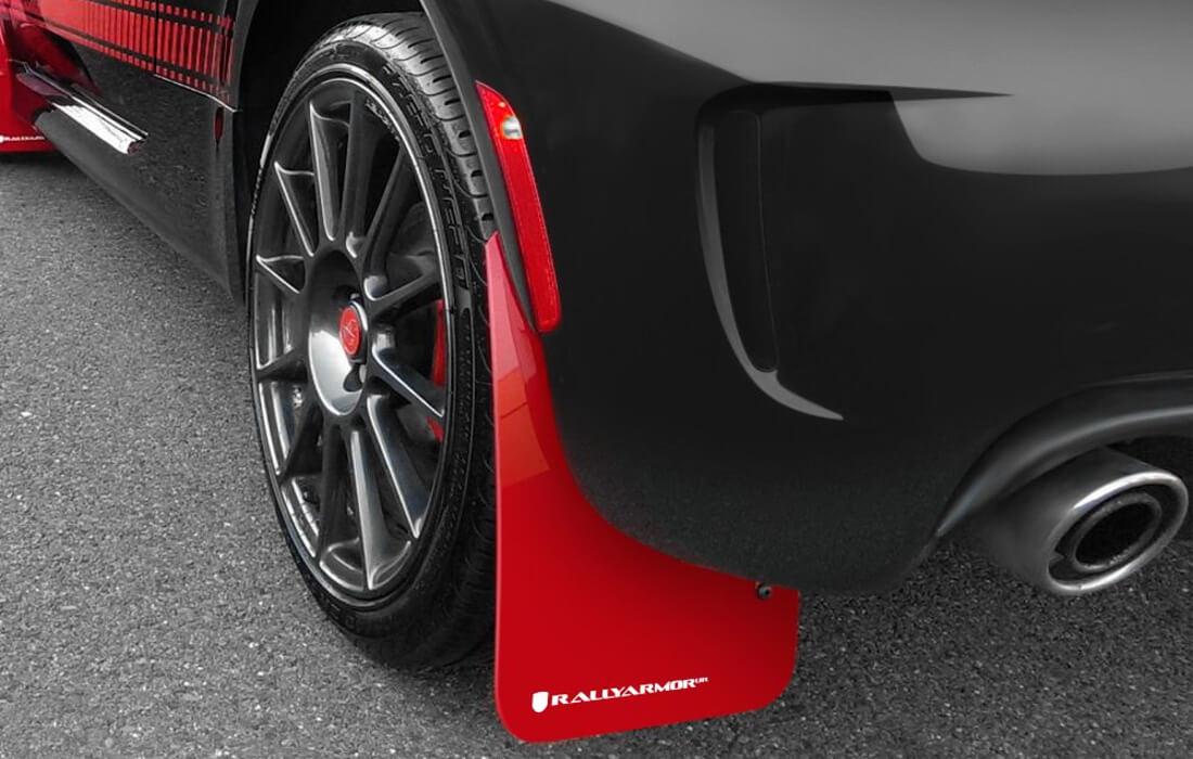 На фото брызговик красного цвета прикреплен к задней подкрылке автомобиля черного цвета