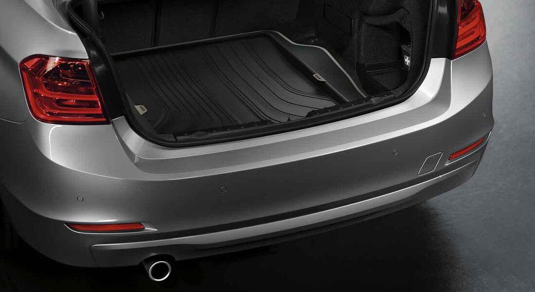 На фото открытое багажное отделение автомобиля, в котором лежит полиуретановый коврик багажника