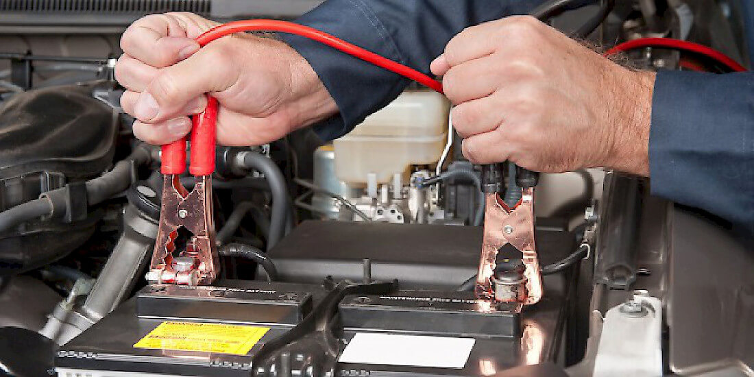 На фото показана замена аккумулятора мастером станции техобслуживания