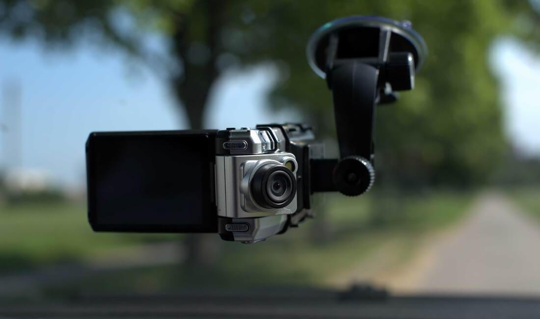 На фото на лобовом стекле автомобиля прикрепленный на присоске видеорегистратор с аккумулятором